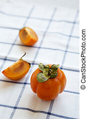 Fresh persimmon on cloth, side view. Close-up.