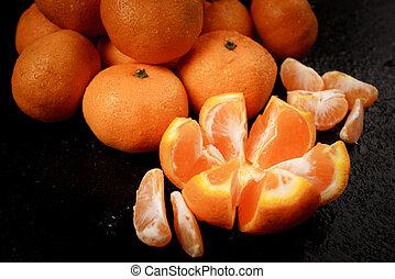 Fresh picked mandarins on black background