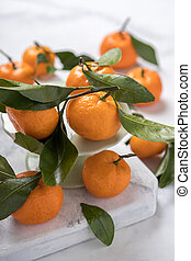 Fresh picked mandarins with leaves on a table