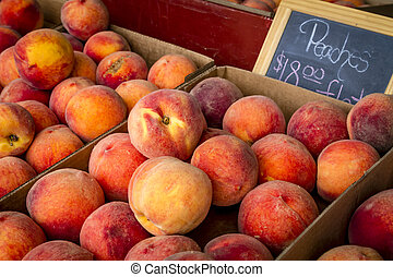 Fresh picked peaches from orchard - Display of boxes filled...