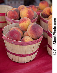 Fresh Picked Ripe Peaches in a Basket at a Farmers Market -...