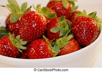 Fresh picked strawberries in a white bowl.
