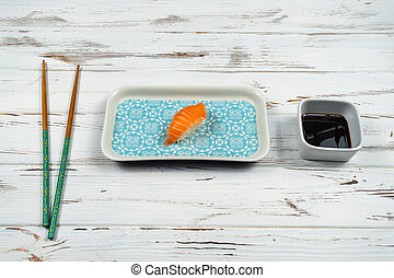Fresh piece of nigiri sushi with wooden chopsticks isolated on a white rusty background