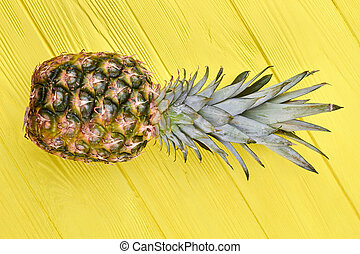 Fresh pineapple on colorful wooden background.