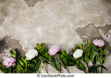 Fresh pink peonies flowers on aged wooden background. Flat lay. Top view with copy space. Selective focus. Toned image.