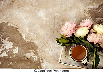 Fresh pink peonies flowers on aged wooden background. Flat lay. Top view with copy space. Toned image.