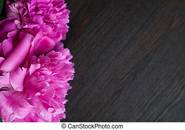 pink peonies on rustic wooden background