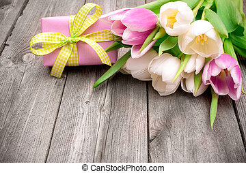 fresh pink tulips with a gift box on wooden background