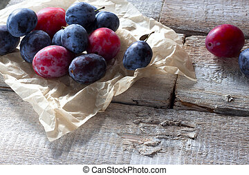 Fresh plum fruit on rustic white wood.
