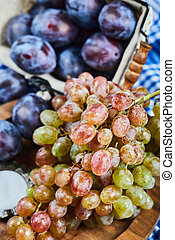 Fresh plums and a bunch of grapes on a plate