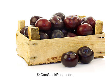 fresh plums in a wooden crate