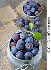 Fresh plums in bowl on the wooden table, top view