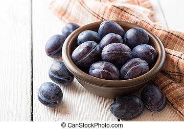 Fresh plums in ceramic bowl on white wooden background.