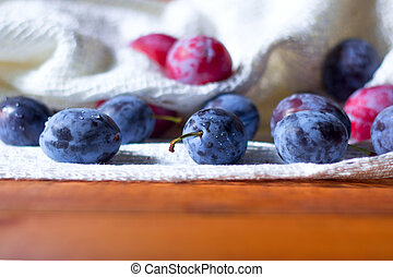fresh plums on wooden table.
