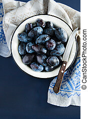 Fresh plums (prunes) in a bowl with a knife