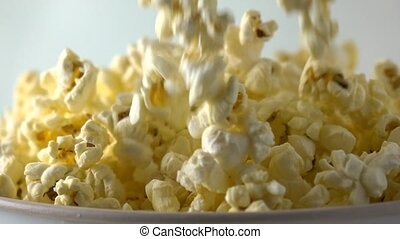 Fresh popcorn falling into paper box. Cinema, overflow or...