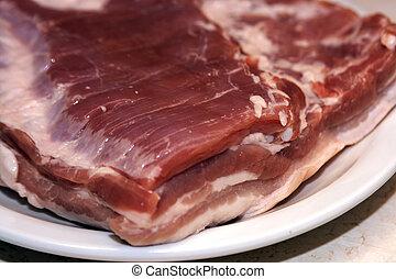 fresh pork bacon on white plate