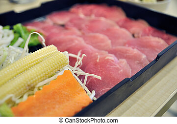 Fresh pork with many vegetables in black tray on table.