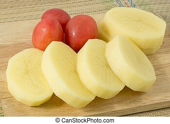 Fresh Potatoes and Tomatoes on Wooden Board