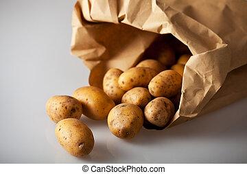 fresh potatoes in a brown paper bag