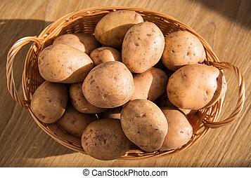 Fresh potatoes in a wicker basket on a wooden table.