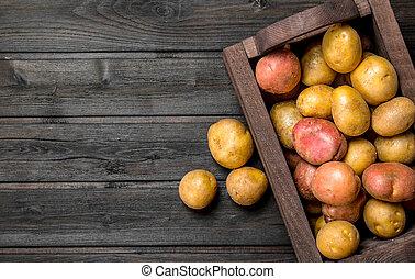 Fresh potatoes in a wooden box.