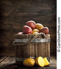 Fresh potatoes in a wooden bucket.