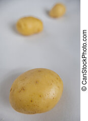 Fresh potatoes isolated on a white table with blurry background