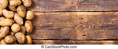 fresh potatoes on wooden table