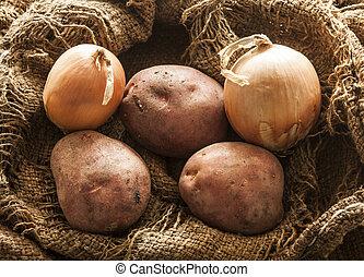 fresh potatos and onion in burlap sack bag