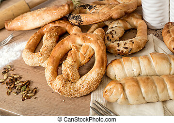 Fresh Pretzel with sesame seeds on the light wooden table. Copy space. Angle top view