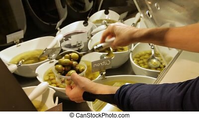 Hands of a shopper are seen close up, picking green olives from a deli counter and placing them in a small plastic container. Local and organic retail.