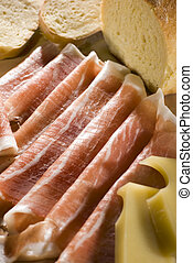 fresh prosciutto with cheese and bread close up shoot