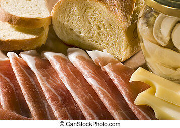 fresh prosciutto with cheese mushrooms and bread close up shoot