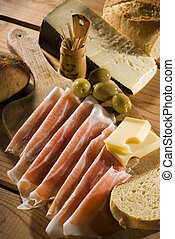 fresh prosciutto with cheese olives and bread close up shoot