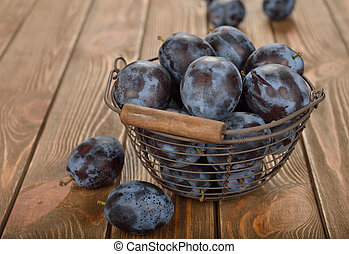 Fresh prunes in a basket on a brown background