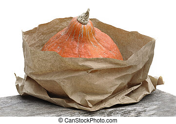 fresh pumpkin in a brown paper bag put on a table on white background