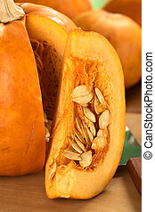 Fresh pumpkin slice with pumpkin seeds (Selective Focus, Focus on the front of the seeds)