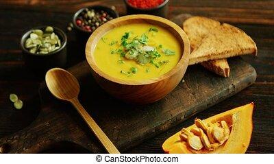 Fresh pumpkin soup in bowl on chopping board