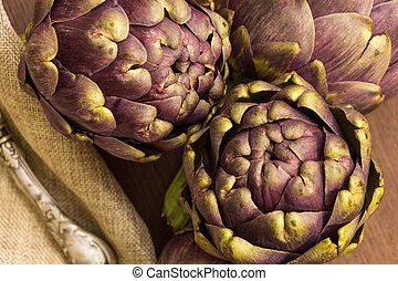 Fresh purple artichokes on wooden surface closeup background