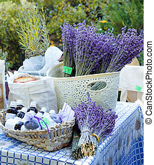 Fresh purple lavender with flacons of essential oil for aromatherapy, alternate medicine and perfumery at market stall.
