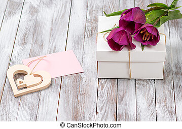 Fresh purple tulips bouquet and gift box on wooden background. Space for text. Decorative heart.