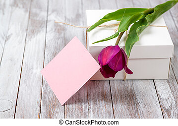 Fresh purple tulips bouquet and gift box on wooden background. Space for text.
