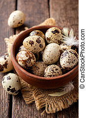 Fresh quail eggs in ceramic bowl on rustic wooden background