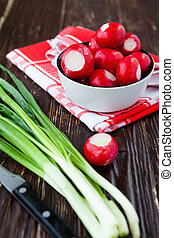 fresh radishes in a bowl and green onions