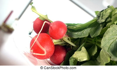 Fresh radishes rotating on a white plate against blurry background