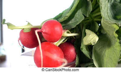 Fresh radishes rotating on a white plate