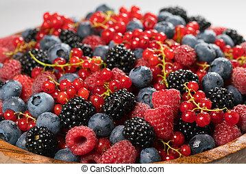 Fresh raspberries, blackberries, redcurrant and blueberries in a wooden bowl