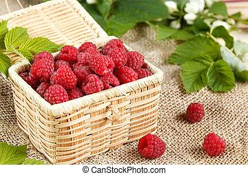 Fresh raspberries in a wicker box and honey, green leaves