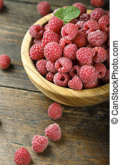 Fresh raspberries in a wooden bowl on a wooden table